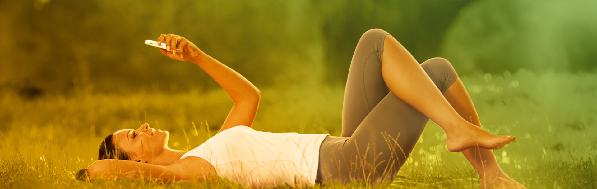 Woman laying on the grass considering a loan on her mobile phone